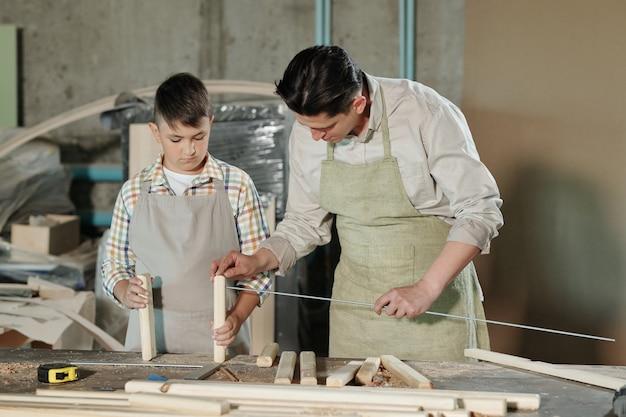 Bekwame man in schort metalen stok tussen houten planken zetten tijdens het monteren van meubels met zoon in werkplaats