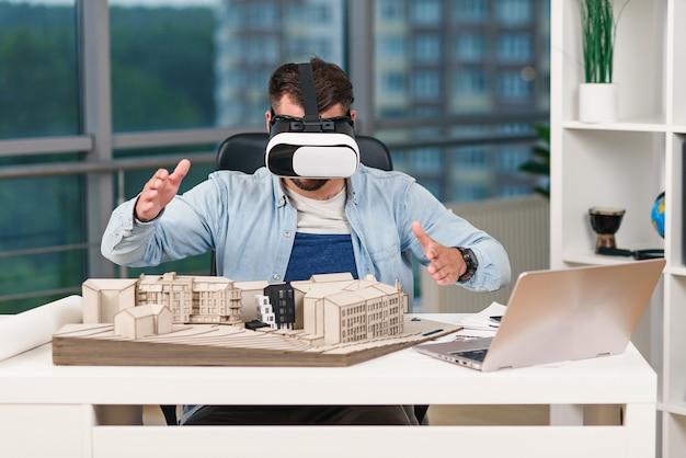 Bekwame mannelijke architect architecturaal project met vr-bril op moderne kantoor herzien.