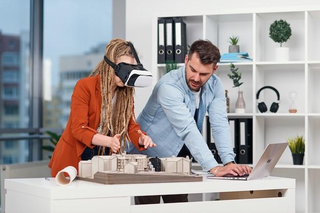 Bekwame mannelijke architect die op laptop werkt terwijl zijn vrouwelijke collega in vr-bril mockup van gebouw analyseert