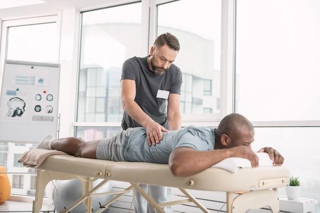 Bekwame orthopedist. ervaren bebaarde man doet een rugmassage voor zijn patiënt terwijl hij werkt als orthopedist