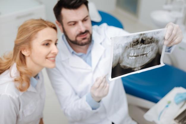 Bekwame privé-tandarts die zijn toekomstige collega-scans van zijn patiënt laat zien, haar enkele details uitlegt en om haar mening vraagt