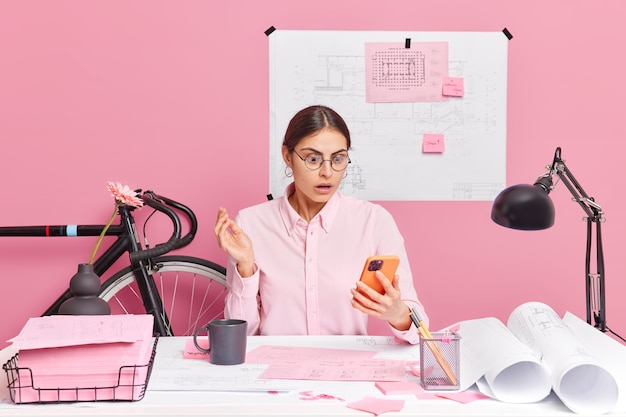 Bekwame professionele vrouwelijke ingenieur geconcentreerd op smartphone-display met geschokte uitdrukking maakt tekeningen creats blauwdrukken poses op desktop