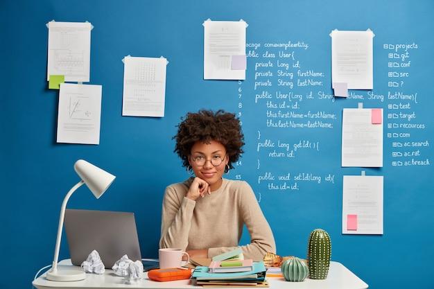 Bekwame tevreden freelancestudent kijkt naar streaming zakelijk nieuws, zit in een goed humeur op de coworking-ruimte met geopende laptopcomputer, denkt na over ideeën voor een nieuw wetenschappelijk project