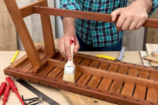 Bekwame timmermansarbeider die zijn hulpmiddelen op hout gebruikt