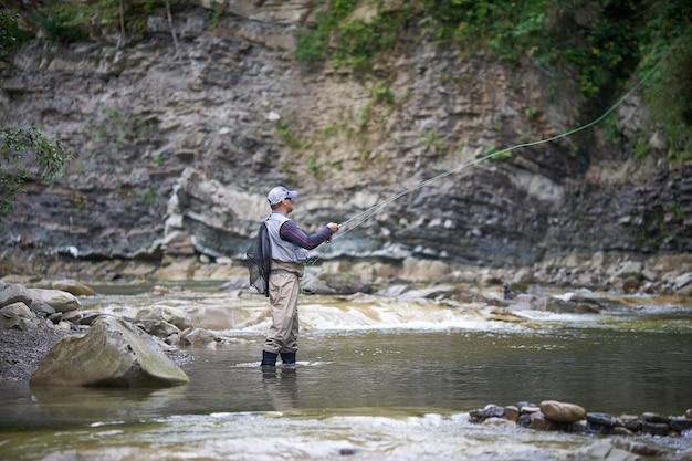 Bekwame visser in uniform en pet met hengel in ruige rivier tussen bergen. concept van visserij en favoriete hobby.