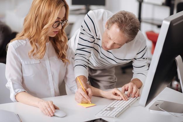 Bekwame vriendelijke bekwame officemanager die op kantoor staat en nieuwkomer helpt tijdens het werken aan het project en het maken van aantekeningen