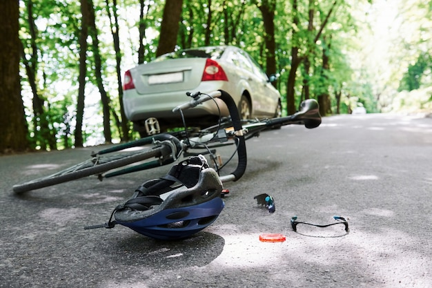 Bel een noodgeval. fiets- en zilverkleurig auto-ongeluk op de weg bij bos overdag