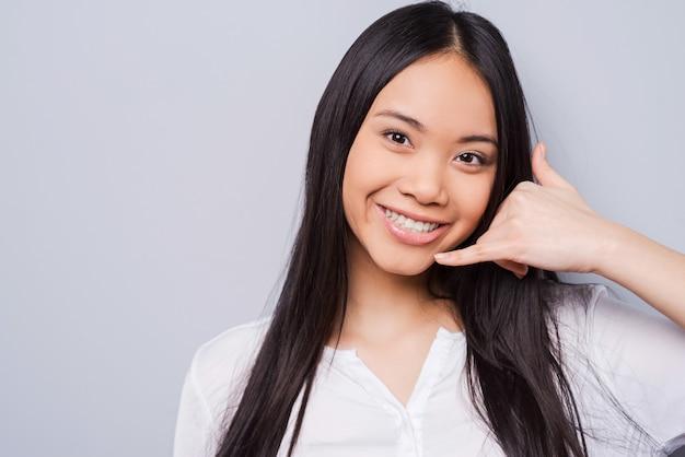 Bel me! aantrekkelijke jonge aziatische vrouw die naar de camera kijkt en gebaren maakt terwijl ze tegen een grijze achtergrond staat