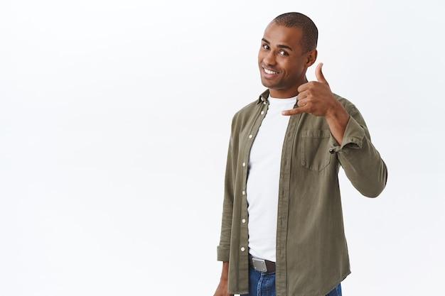 Bel me een keer. portret van brutale, knappe zelfverzekerde afro-amerikaanse man toont telefoonbord bij hoofd en glimlacht