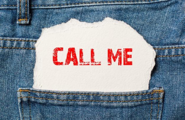 Bel me op wit papier in de zak van een blauwe spijkerbroek