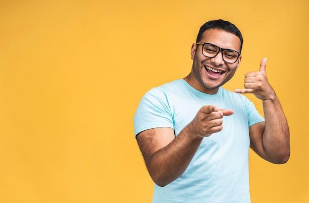 Bel me teken. portret van een gelukkig afro-amerikaanse indiase zwarte man praten op mobiele telefoon geïsoleerd op gele achtergrond.