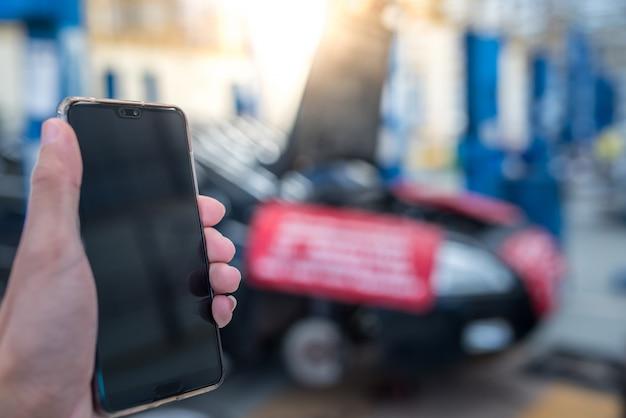 Bel met een mobiele telefoon naar een automonteur omdat de auto kapot was.