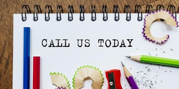 Bel ons vandaag tekst geschreven op papier met potloden in kantoor