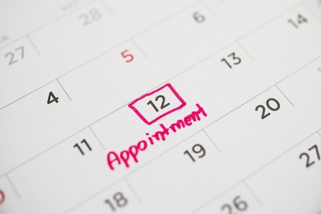 Belangrijk afspraakschema schrijven op witte kalenderpagina datum close-up