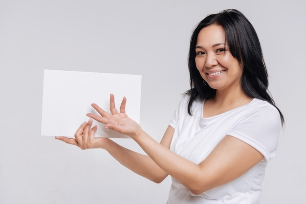 Belangrijk bericht. leuke stijlvolle petite vrouw die een blanco vel papier vasthoudt en ernaar wijst met haar hand terwijl ze poseert in vrijetijdskleding