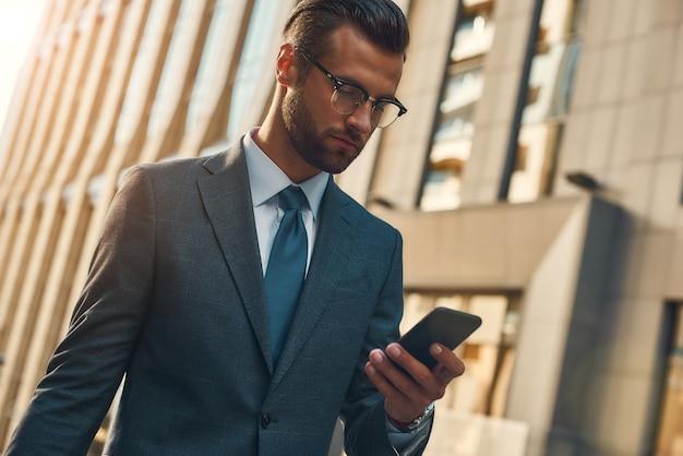 Belangrijk bericht portret van knappe bebaarde zakenman in formele kleding met behulp van slimme telefoon terwijl