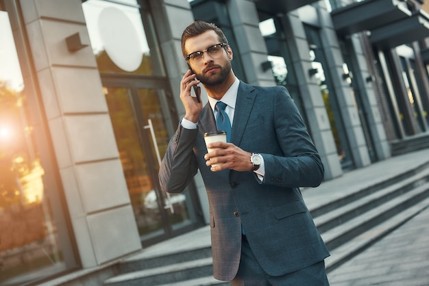 Belangrijk gesprek jonge en knappe bebaarde zakenman in formele kleding die telefonisch praat en vasthoudt Premium Foto