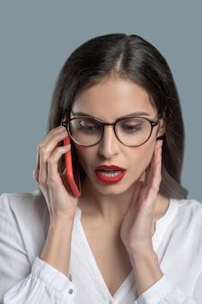 Belangrijk gesprek. mooie zakelijke jonge vrouw met open mond praten over smartphone ernstig gericht