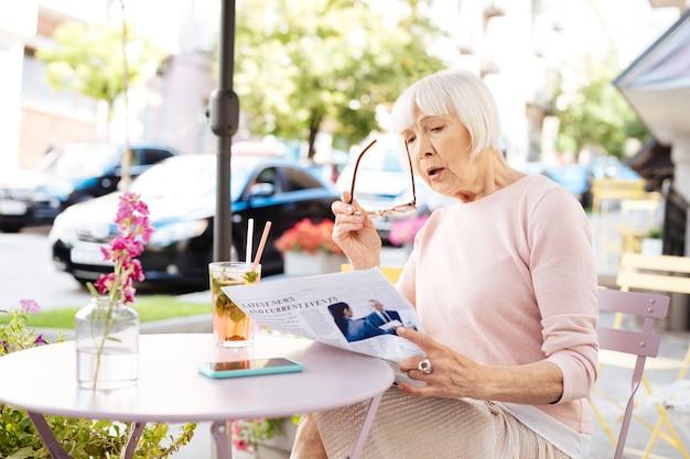 Belangrijk nieuws. verbaasd senior vrouw krant lezen en bril te houden