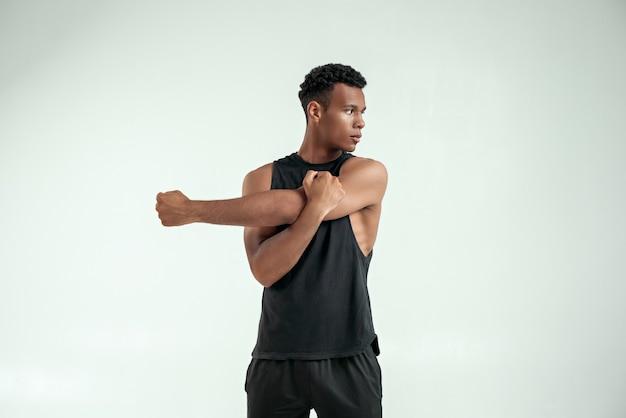 Belangrijk strekken. sterke jonge afro-amerikaanse man die zijn arm uitstrekt terwijl hij tegen een grijze achtergrond staat. sportconcept. actieve levensstijl