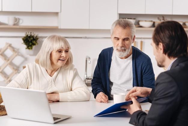 Belangrijke beslissing nemen. opgetogen vriendelijke senior paar om thuis te zitten achter de laptop en een gesprek met makelaar terwijl het uiten van interesse
