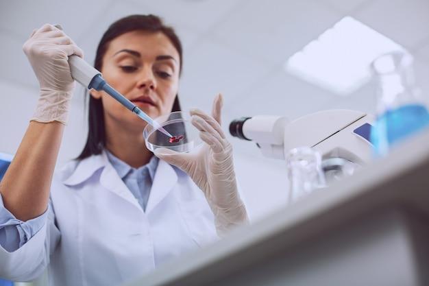 Belangrijke bloedtest. ernstige slimme wetenschapper die een bloedtest uitvoert en een uniform draagt