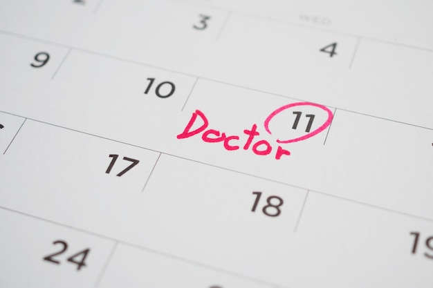 Belangrijke dokter afspraak schema schrijven op witte kalender pagina datum close-up