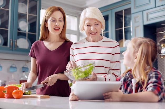 Belangrijke hulp. lief klein meisje dat een recept op de tablet aan haar moeder en grootmoeder toont terwijl de vrouwen salade maken en het recept controleren