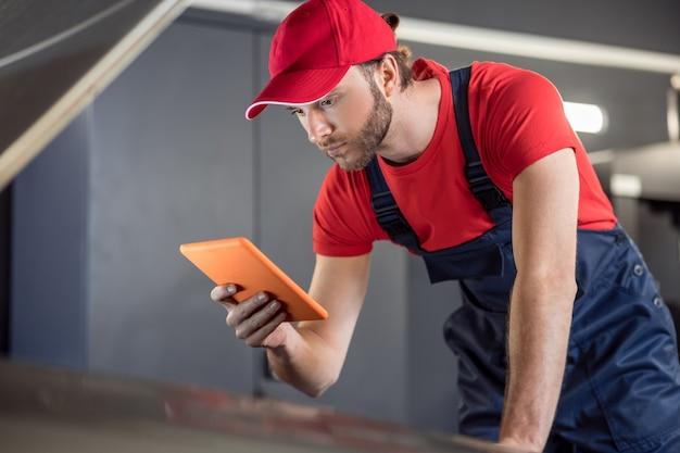 Belangrijke informatie. betrokken jonge bebaarde man in overall kijken met interesse naar tablet onder motorkap van auto in werkplaats
