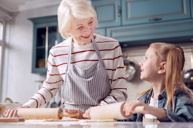 Belangrijke les. gelukkige senior vrouw in een schort die haar kleine kleindochter uitlegt hoe ze deeg moet uitrollen terwijl ze liefdevol naar haar glimlacht
