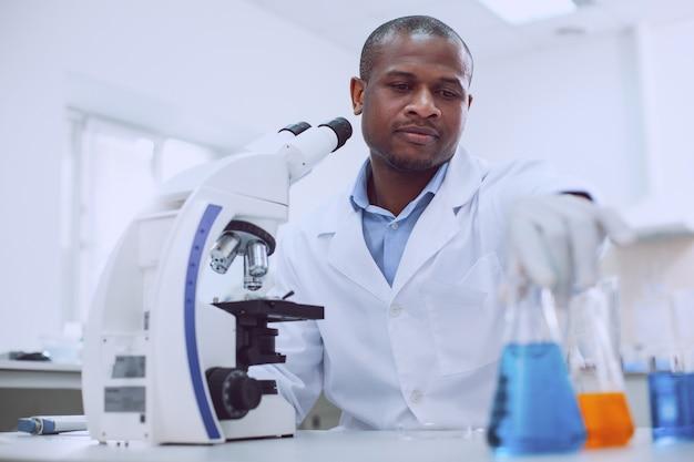 Belangrijke vloeistoffen. ernstige ervaren bioloog die met zijn microscoop werkt en een buis aanraakt