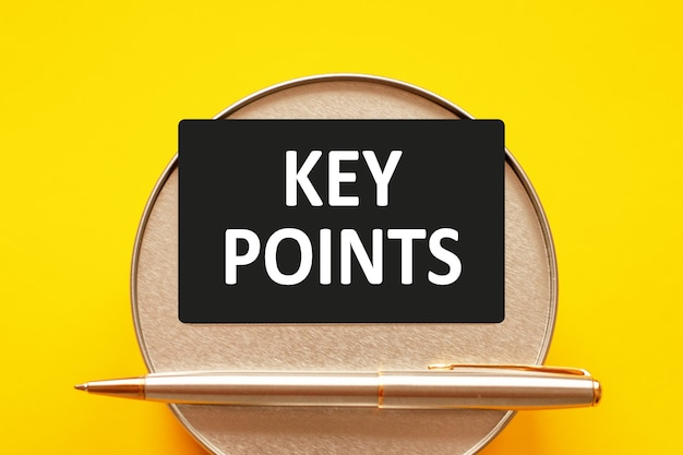 Belangrijkste punten - woorden die witte letters op een vel papier schrijven. zwarte kaart met tekst op een gele achtergrond met ronde metalen standaard en metalen schrijfpen. zakelijk en financieel concept