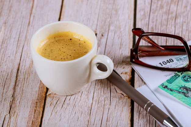 Belasting 1040 formulieren met zwarte koffie en pen met amerikaanse individuele inkomstenbelasting en glazen