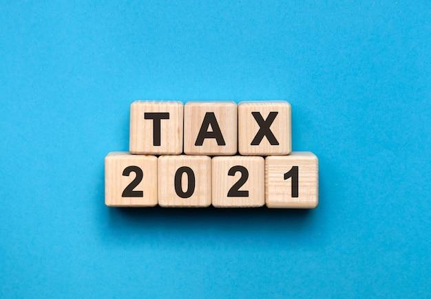 Belasting 2021 - tekstconcept op houten kubussen met blauwe achtergrond met kleurovergang.