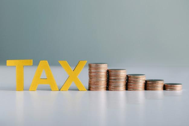 Belasting concept. woord belasting en gestapelde munten op witte tafel