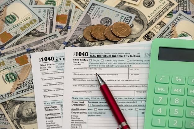 Belasting- en boekhoudkundig concept, 1040 formulierpencalculator en dollarbiljetten