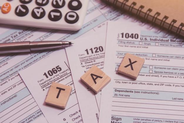 Belasting met houten alfabet blokken, rekenmachine, pen op 1040 belastingformulier