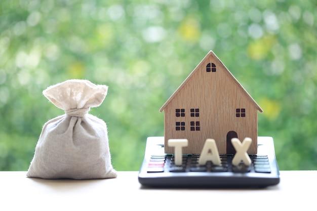 Belasting op onroerend goed, modelhuis op rekenmachine met geldzak op natuurlijke groene achtergrond, bedrijfsinvesteringen en geld besparen om in toekomstig concept voor te bereiden
