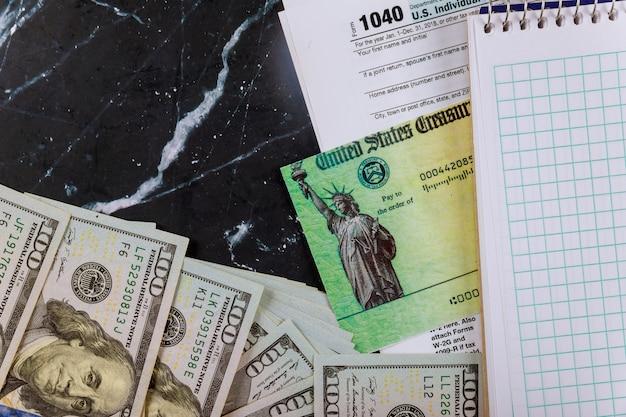 Belastingaangifte en terugbetaling cheque amerikaanse belastingformulier, dollar contant en blanco notebook 1040 individuele belastingformulier