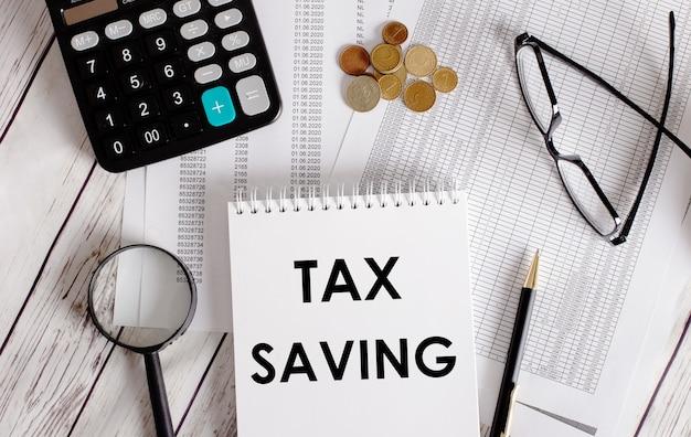 Belastingbesparing geschreven in een wit notitieblok in de buurt van een rekenmachine, contant geld, glazen, een vergrootglas en een pen. bedrijfsconcept