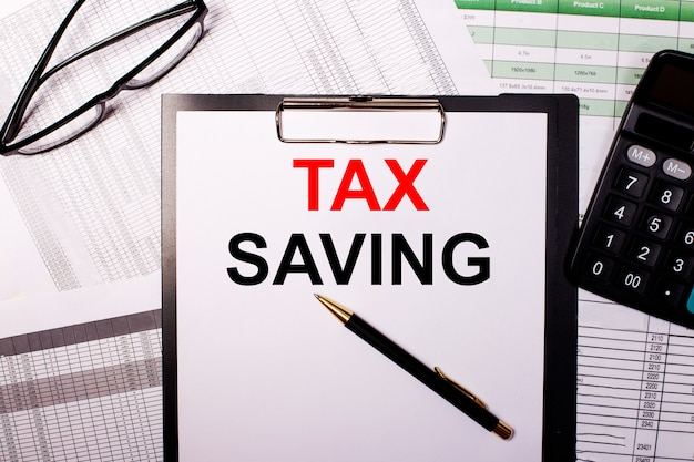 Belastingbesparing staat op een wit vel papier, naast de bril en de rekenmachine