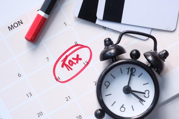 Belastingdag concept met kalender, klok op tafel