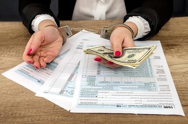 Belastingformulier, handen in handboeien, geld