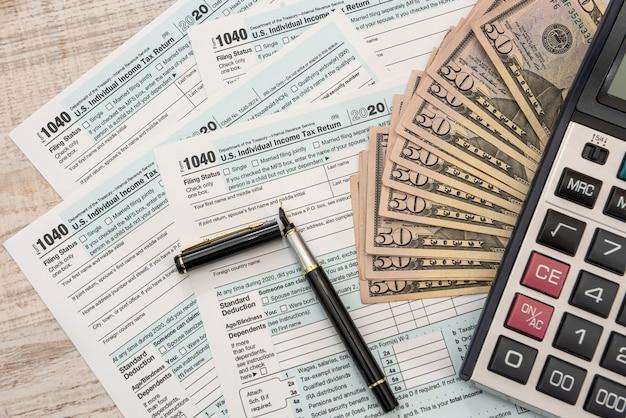Belastingformulieren 1040 met dollars en rekenmachine voor het invullen van april. belastingen concept.
