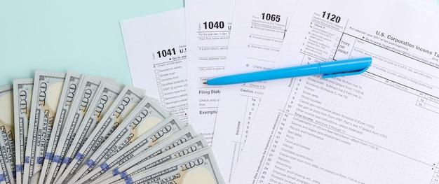 Belastingformulieren liggen in de buurt van honderd dollarbiljetten en een blauwe pen