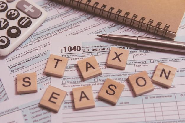 Belastingseizoen met houten alfabetblokken, rekenmachine, pen op 1040 belastingformulier