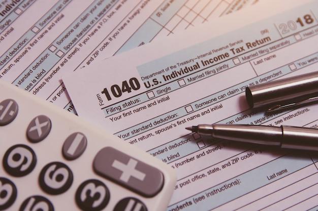 Belastingseizoen. rekenmachine, pen op 1040 belastingformulier
