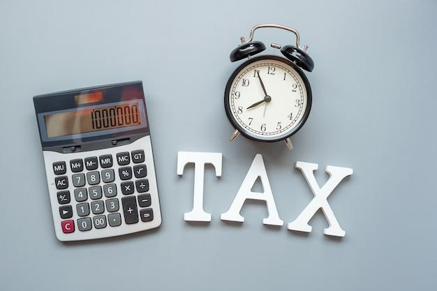 Belastingtekst met rekenmachine en wekker. investeringen en tijd om concepten te belasten