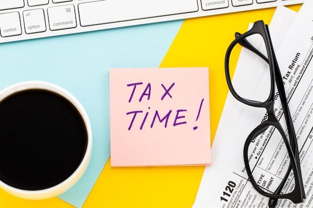 Belastingtijd geschreven op papieren notitie met belastingformulier en kopje koffie.