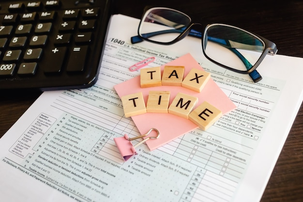 Belastingtijd - houten letters, belastingformulier met sticker, bril en rekenmachine.
